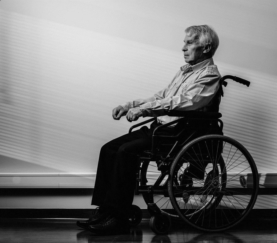 Thoughtful senior man in wheelchair in nursing home