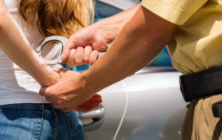 Police officer arresting a woman with handcuffs