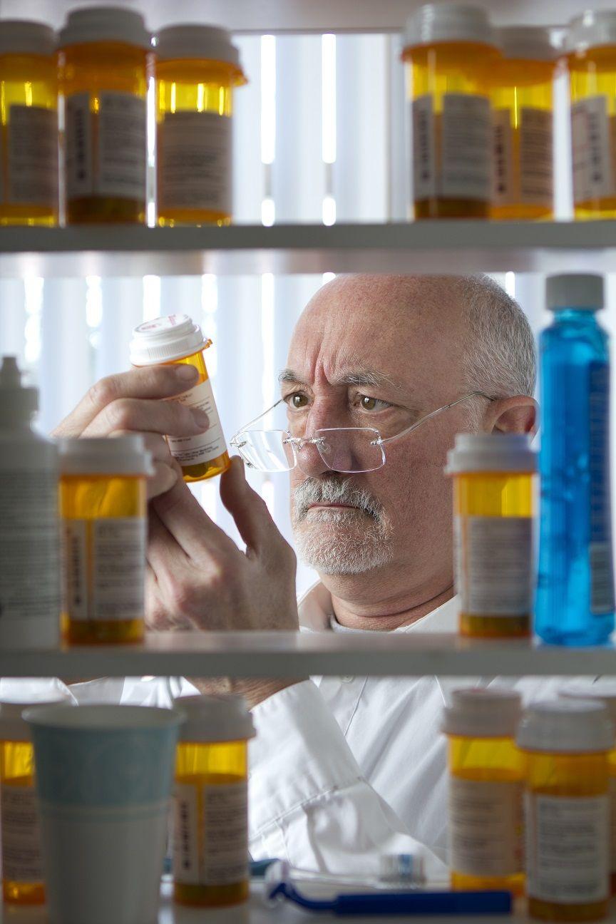 Man reaching for prescription form medicine cabinet