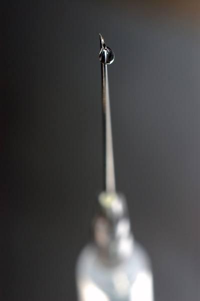 syringe close-up, focus on the drop