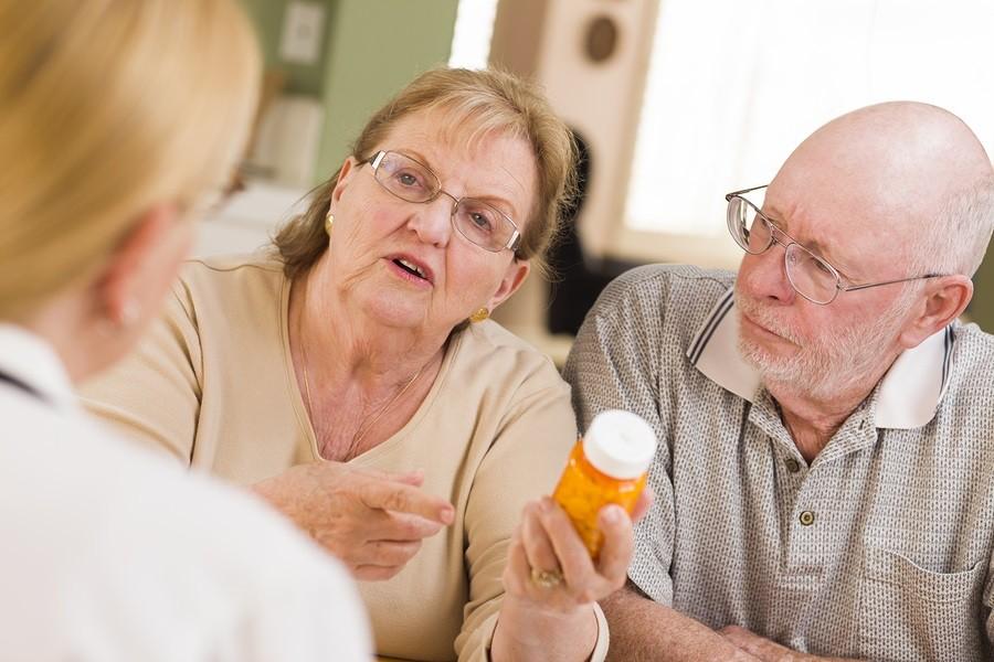 Doctor or Nurse Explaining Prescription Medicine to Attentive Se