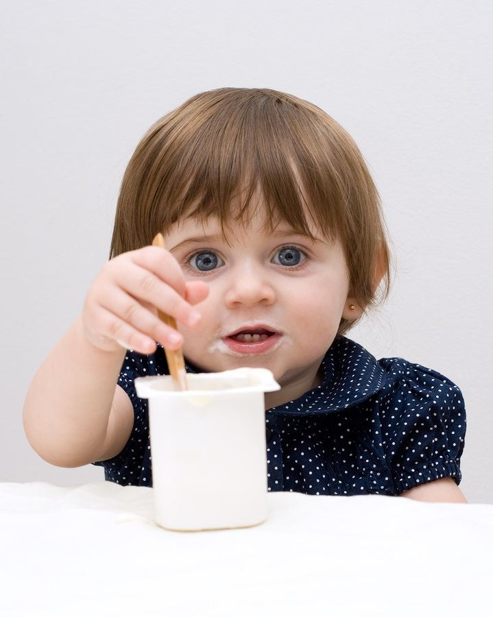 Portrait of the little girl with yogurt