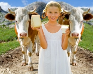 Milk fresh from the cow - lovely girl with dairy products and co