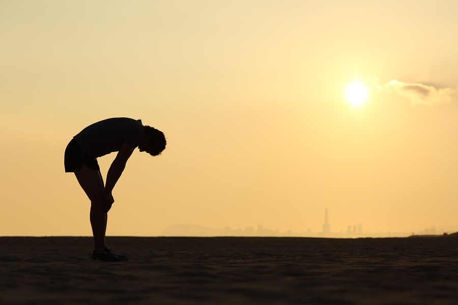Silhouette Of An Exhausted Sportsman At Sunset