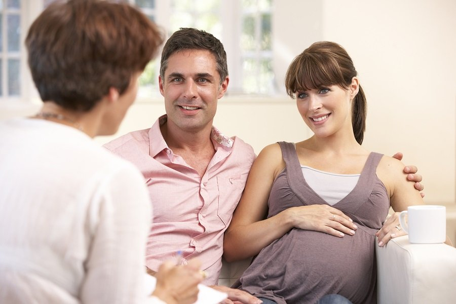 Expectant couple talking to midwife photo