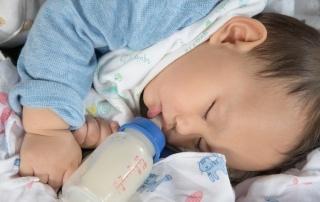 cute Asian baby boy sleep drinking milk on the bed