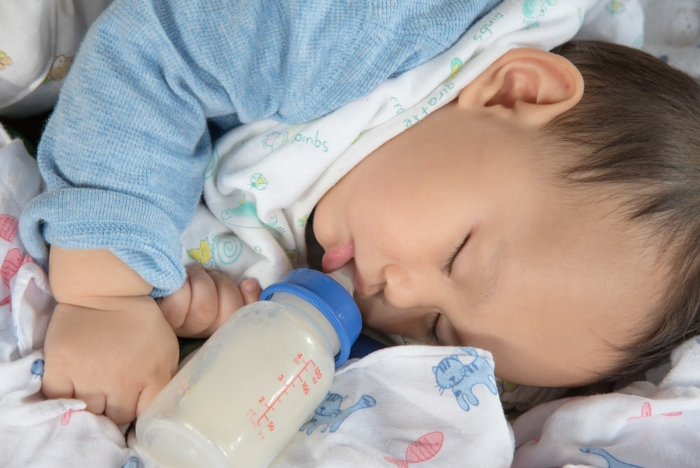 cute Asian baby boy sleep drinking milk on the bed