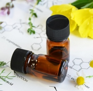 essential oils with herbal flowers on science sheet