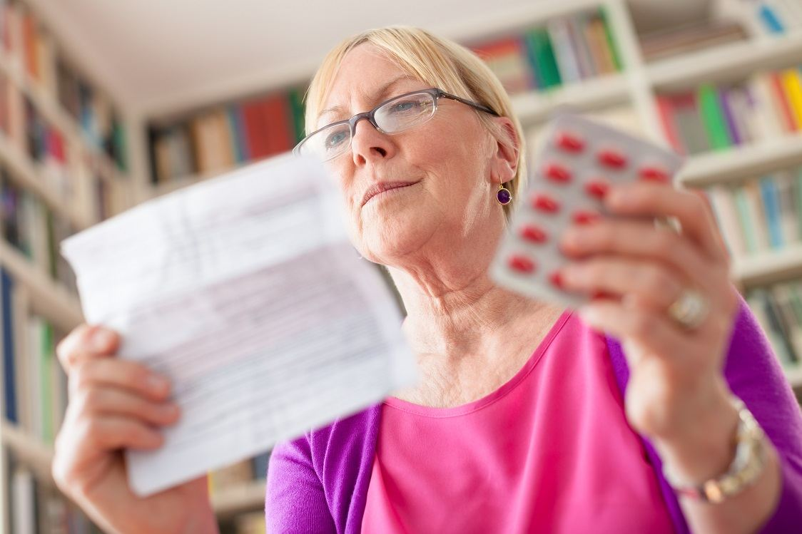 Elderly caucasian woman with medicine and reading drug prescription. Low angle view