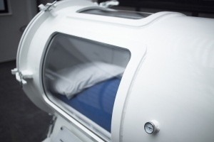 Hyperbaric Oxygen Therapy (HBOT) chamber tank used for specialised medical treatment for injuries in hospital clinic. Exterior viewing window and reflection with pillow and bed inside.