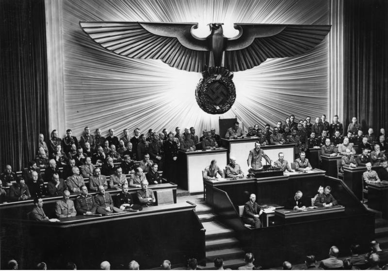 Die vernichtende Rede des Führers über Roosevelt. Am Donnerstag nachmittag hielt der Führer vor den Männern des Deutschen Reichtags die grosse und mit fieberhafter Spannung erwartete Rede zu dem von dem Kriegshetzer Roosevelt heraufbeschworenen Krieg im Pazifik. Auf der Regierungsbank (von rechts nach links) sieht man den Führer, neben ihm Reichsaussenminister v. Ribbentrop, Grossadmiral Reader, Generalfeldmarschall v. Brauchitsch, Generalfeldmarschall Keitel und die Reichsminister Dr. Frick und Dr. Goebbels. In der zweiten Reihe (von rechts): Die Reichsminister Graf Schwerin-Krosigk, Funk, Darré, Rust, Kerrl, Dr. Frank, Dr. Dorpmüller, Dr. Seyss-Inquart und Dr. Todt. Dahinter (von rechts): Reichsminister Rosenberg und die Staatsminister Dr. Meissner und Dr. Popitz. AV 65979