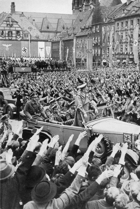 Hitler (standing in the Mercedes) drives through the crowd in Cheb