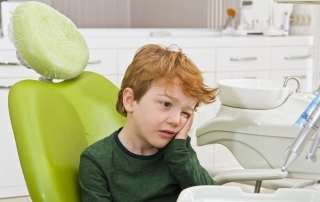 examining teeth of small patient at dentist. child with toothache sitting in a dentist chair