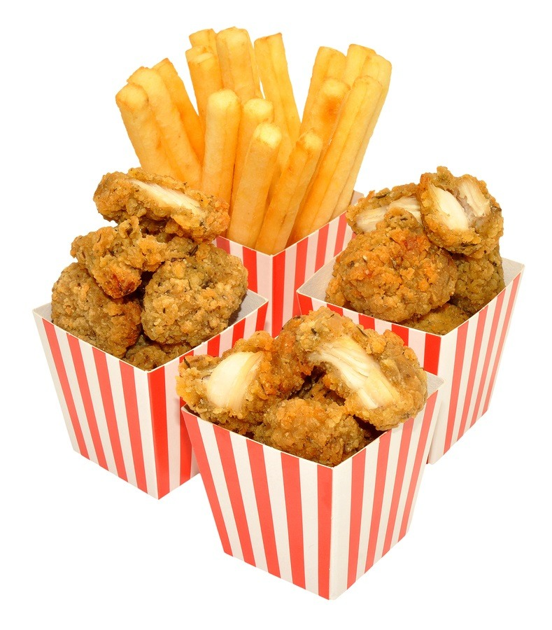 Southern fried chicken nuggets and French fries in red and white striped boxes, isolated on a white background.