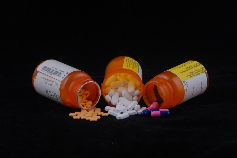 Photos shows three prescription medication bottles with the pills spilling out. You can not identify the patient information on the labels but enough of the label is visible to show it is a real prescription.