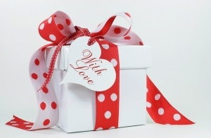 Red and white polka dot theme gift box present with heart shape gift tag with love for Christmas Valentine birthday wedding or special occasion.