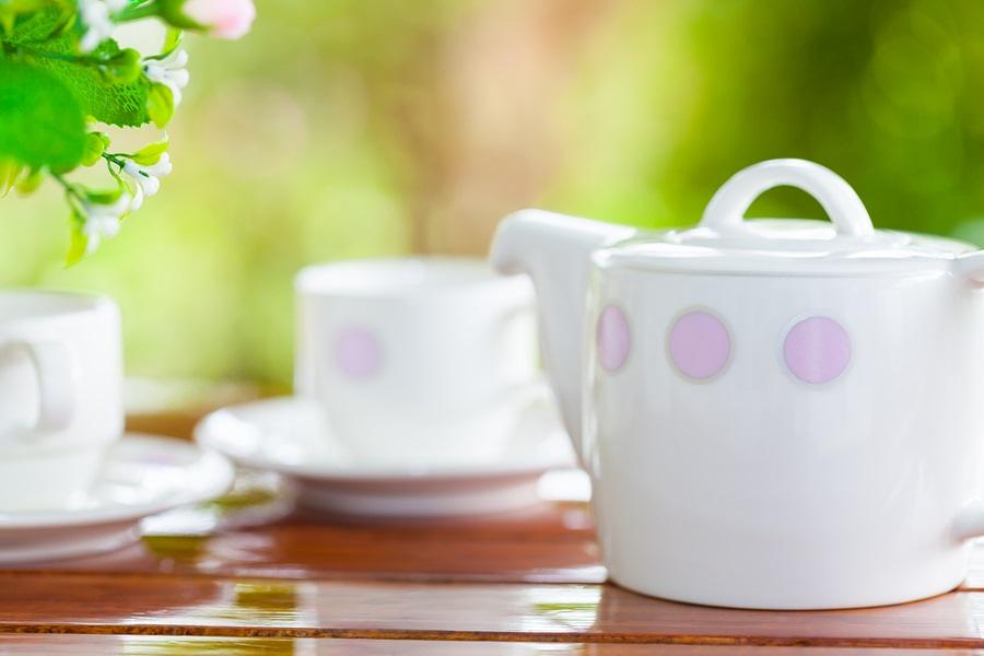 White porcelain set for tea or coffee on wooden table in the garden over blur green nature background shallow DOF teapot in focus