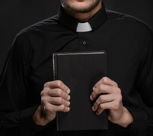Priest holding Bible. Portrait of priest reading the Holy Bible