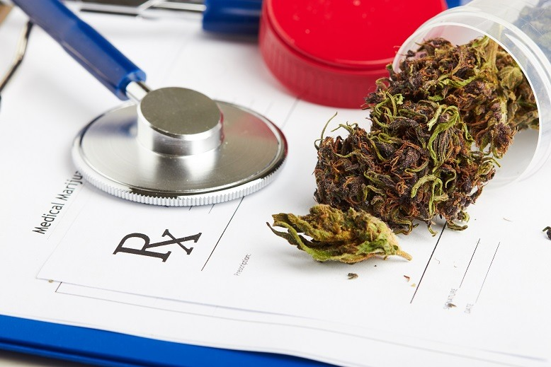 Medical marijuana in jar lying on prescription form near stethoscope.