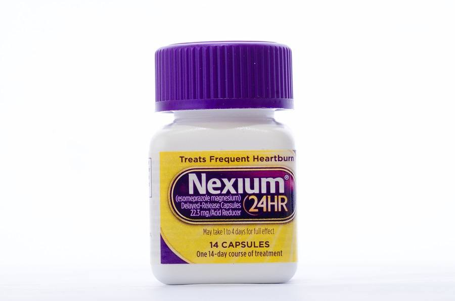 "LLANO TX-AUG 16 2015: Bottle of Nexium against white background. The ""Purple Pill"" now sold in ""Non-Prescription"" size dosage."