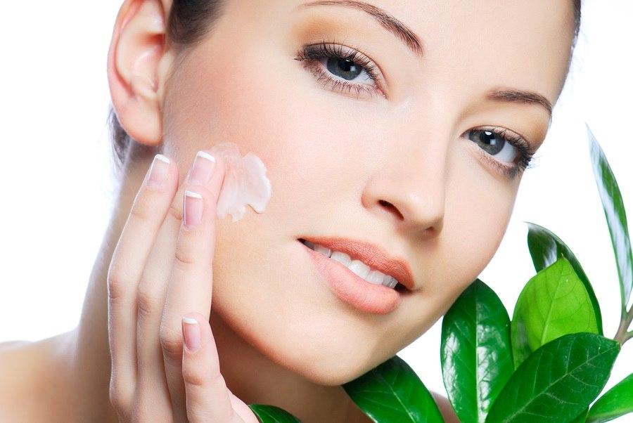 Woman applying moisturizer cream on face. Close-up fresh woman.