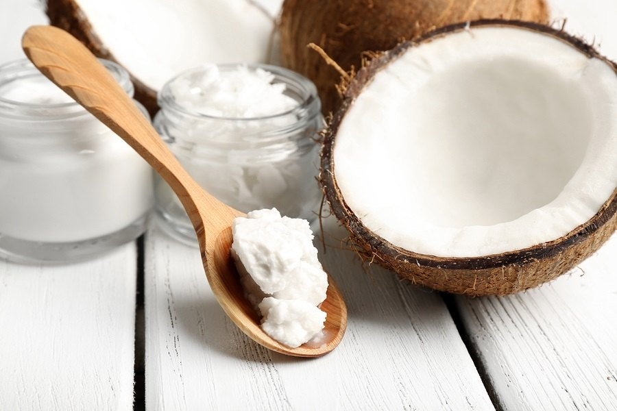 Coconut with jars of coconut oil and cosmetic cream on wooden background