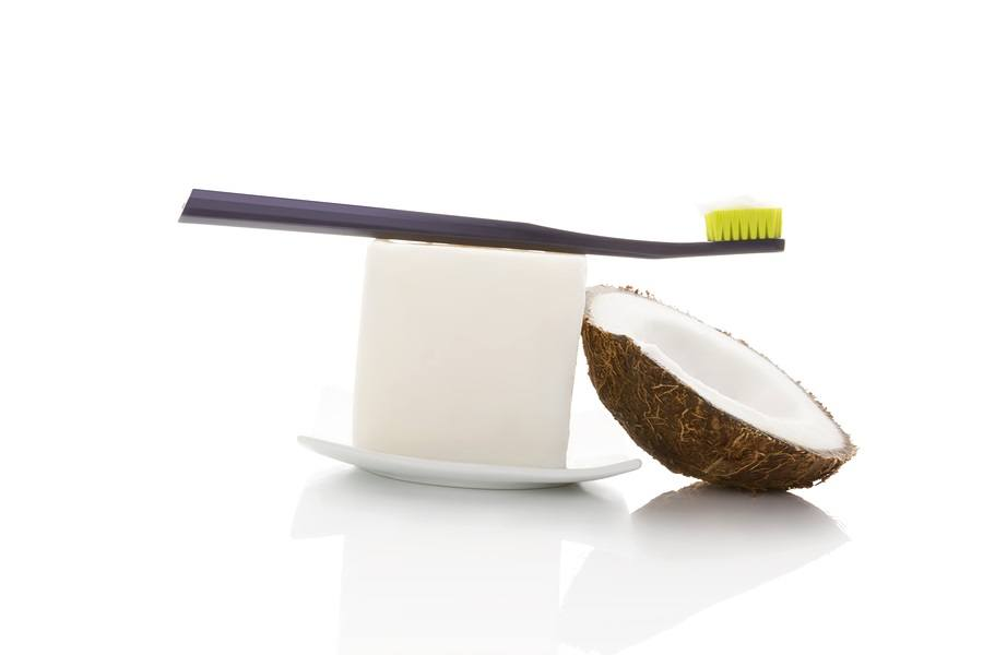 Hard organic coconut oil with toothbrush and coconut isolated on white background. Natural organic dental hygiene.
