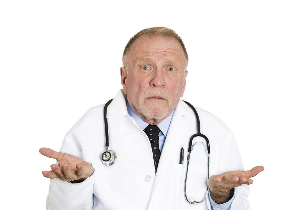 Closeup portrait of clueless senior mature health care professional, old doctor with stethoscope, has no answer, doesn't know right diagnosis, isolated on white background. Emotion facial expression