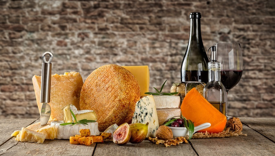 Various types of cheese, glass and bottle of red wine placed on wooden table, copyspace for text. brick wall on background