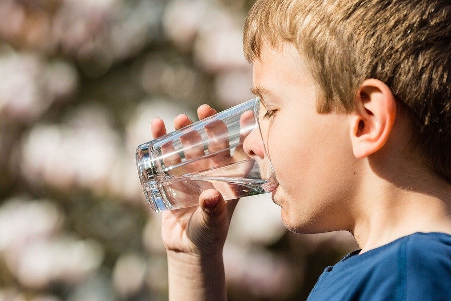 Young boy drinking from glass of fresh water. Ideal for environmental protection or future generations concept.