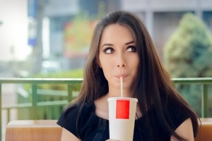 Portrait of a funny girl drinking trough a straw