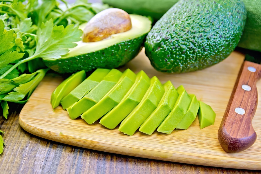 Whole and halved avocado, sliced avocado half, knife, parsley, napkin on a wooden boards background