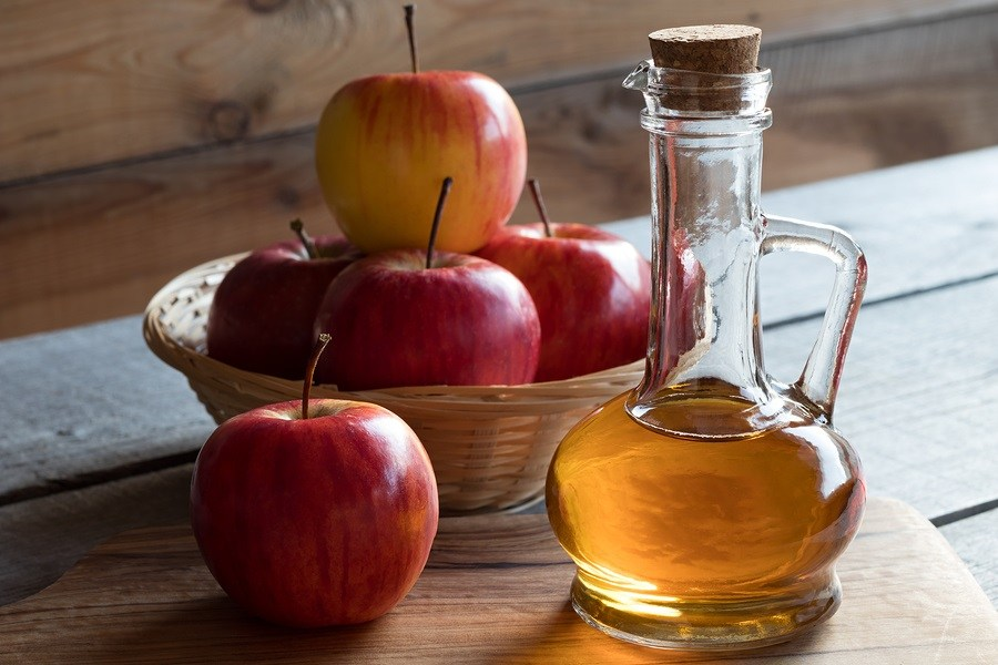 A bottle of apple cider vinegar with apples in the background