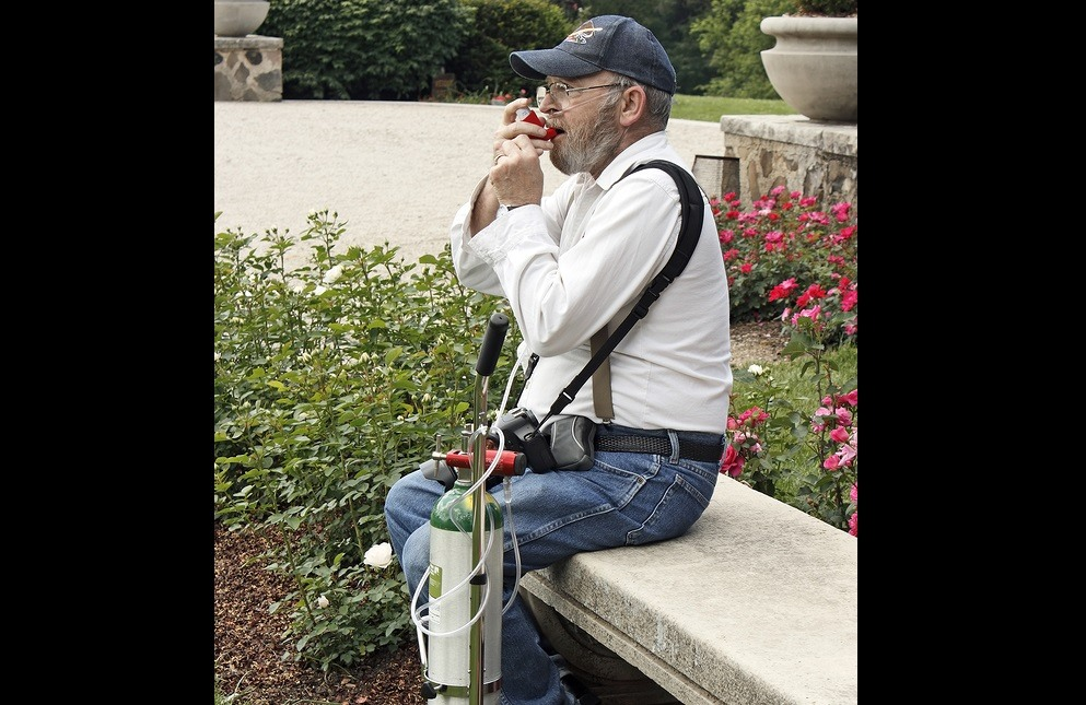Disabled man with a camera enjoying the tourist sights. His life depends on his oxygen tank. Asthma emphysema COPD. He is using a rescue inhaler.