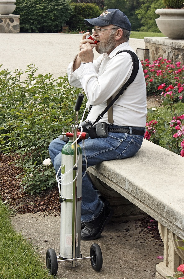 Disabled man. His life depends on his oxygen tank. Asthma emphysema COPD. He is using a rescue inhaler.