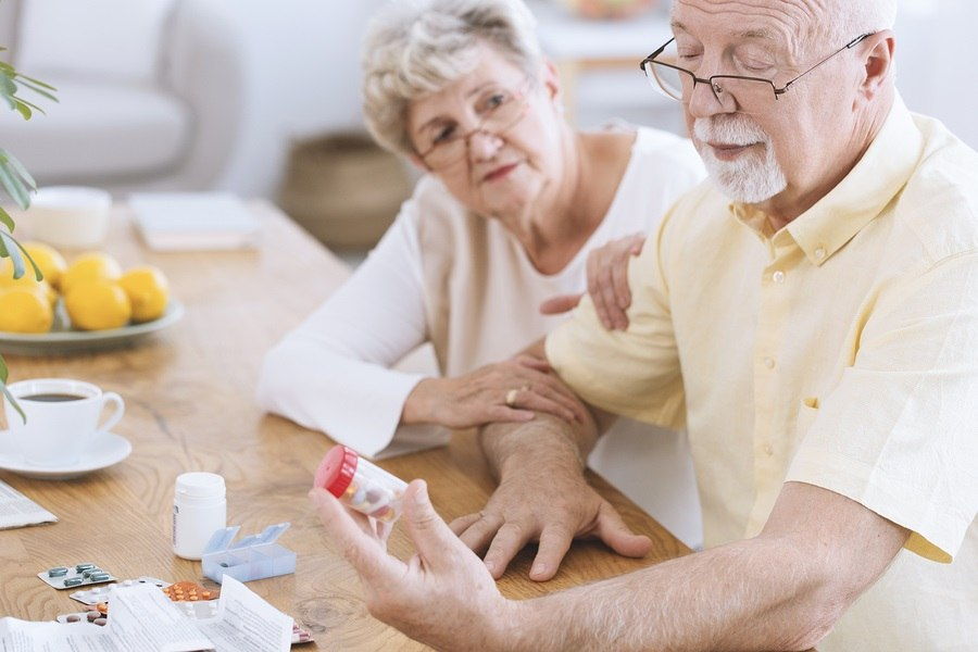 Old couple looking at tablets and sitting at a table with medicine, coffee and prescription