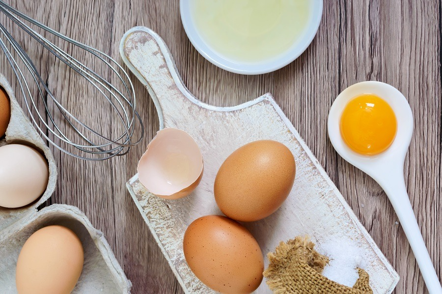 Fresh farm eggs on a wooden rustic background. Separated egg white and yolks, broken egg shells. Whipping eggs with whisk. Preparation of food from chicken eggs. The top view. View from above.