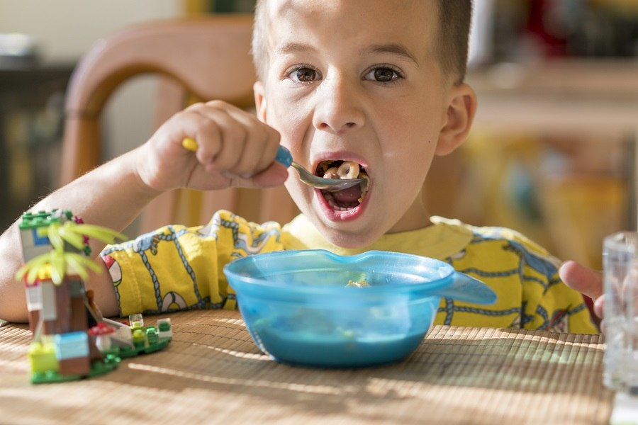 The boy 4 years eats porridge. Children's table. The concept of the child's independence. the boy is breakfasting with an appetite on the kitchen background.