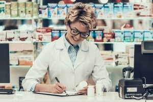 Portrait Smiling Pharmacist Working in Drugstore. Mature Woman Pharmacist wearing White Coat and Glasses writing on Clipboard and Holding Medication in the Pharmacy. Professional Pharmacist at Work