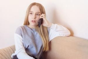 Teen girl holding a phone near her ear