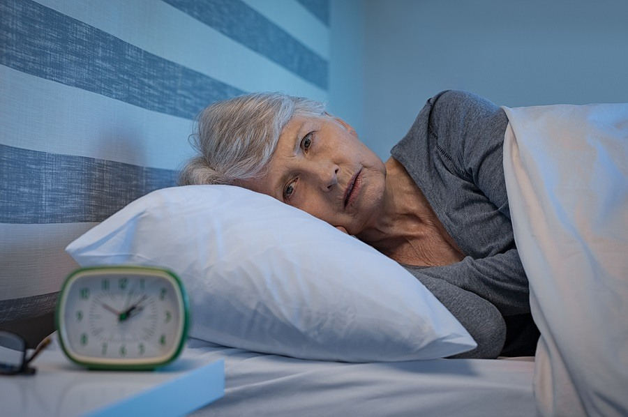 Worried senior woman in bed at night suffering from insomnia. Ol