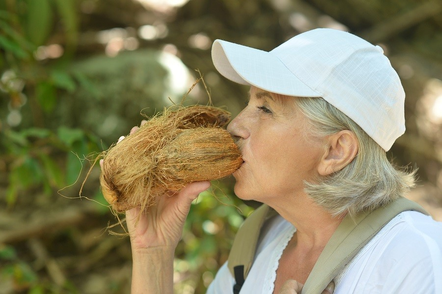 Older woman  tourist with coconut
