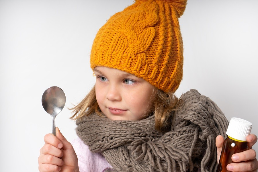 Little woolen dress in a warm scarf and knitted hat. holds in his hands a bottle of cough syrup for colds and looks at the spoon, is going to drink.
