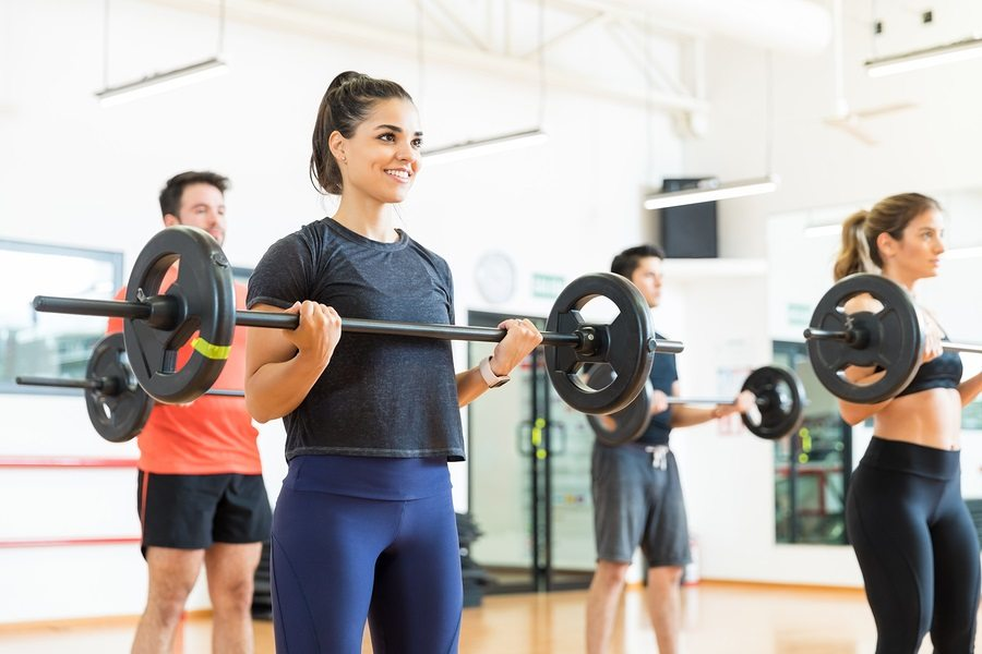 Young woman smiling while lifting barbell by friends in health club