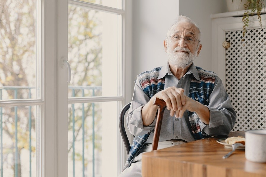 Senior man with grey hair and beard and with walking stick sitting on armchair alone in his apartment