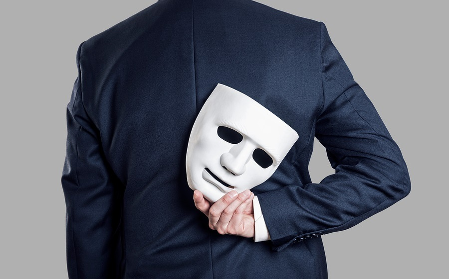 Business fraud concept. Businessman hide the mask in hand behind